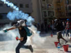 Protesters respond as riot police use tear gas to disperse the crowd during a demonstration near Taksim Square on June 11, 2013 in Istanbul, Turkey. Istanbul has seen protests rage on for days, with two protesters and one police officer killed