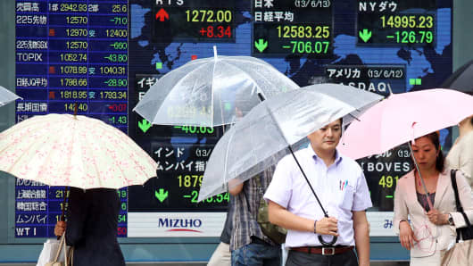 Pedestrians with umbrellas walk past an electronic stock board in Tokyo, Japan.