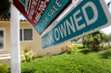 A Bank Owned sign is seen in front of a foreclosed home in Miami, Florida.