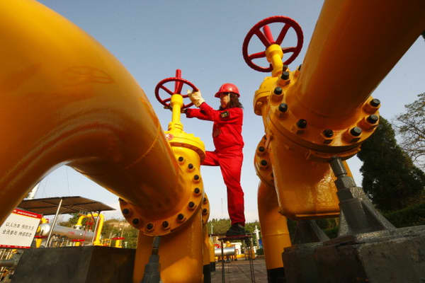 A Chinese worker checks the valve of a gas pipe at a natural gas plant in Suining, in southwest China's Sichuan province.