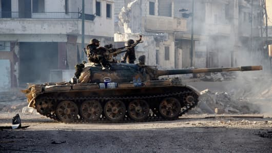 Syrian army troops drive through the ravaged streets of Qusayr in the central Homs province on June 5, 2013, after government forces seized total control of the former rebel-stronghold.