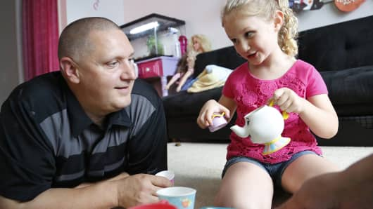 Carl Poff attends a tea party with his daughter Joselyn, 4, in their playroom. The girls love to have tea parties about once a week, Poff said.