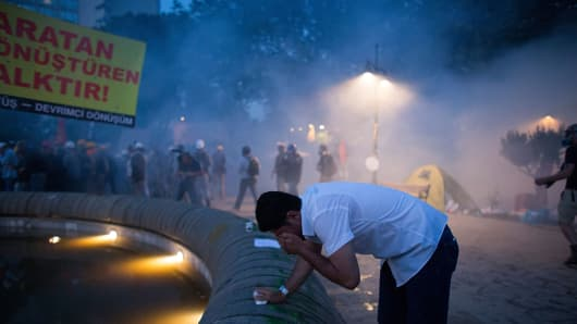 A man cover the eyes after riot police fire tear gas during the crackdown action at Gazi Park on June 15, 2013 in Istanbul, Turkey.