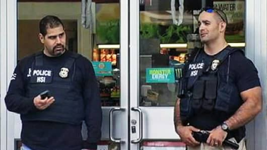Police officers stand outside one of the several 7-Elevens they raided as part of an identity theft and illegal immigration investigation.