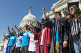 Members of United We Dream, an immigrant youth-led organization, wearing caps and gowns hold their fists in the air on the steps of the Senate to call for immigration reform.