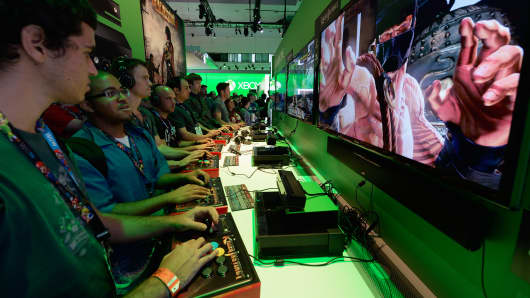 Gamers play a game on the Xbox One console in the Microsoft Exbox Xbox booth during the Electronics Expo 2013 at the Los Angeles Convention Center.