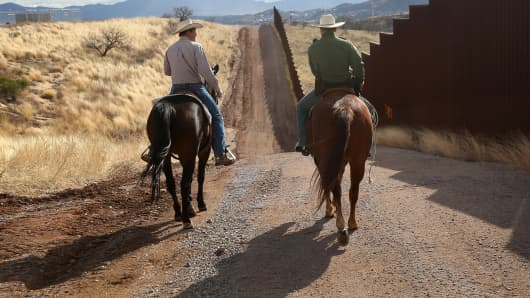 A U.S. Border Patrol agent rides with a cattle rancher at the U.S.-Mexico border.