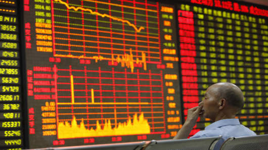 An investor watches the electronic board at a stock exchange hall in Huaibei, China.