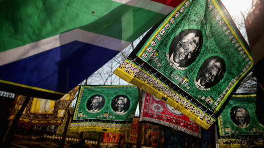 Souvenir flags picturing former South African President Nelson Mandela sway in the wind across from the Hector Pieterson Memorial and Museum in Soweto Township June 24, 2013 in Johannesburg, South Africa.