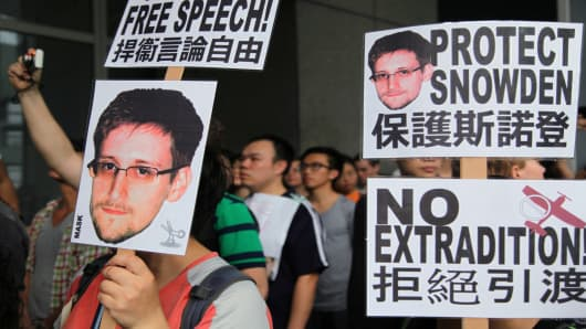 Protesters in Hong Kong hold placards during a rally in support of Edward Snowden.