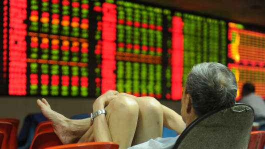An investor watches the electronic board at a stock exchange hall in Hefei, China.
