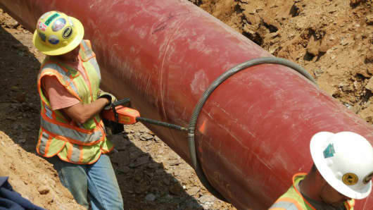 Workers install a natural gas pipeline.