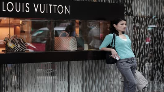 A Chinese woman leaning on a Louis Vuitton shop display window in Hong Kong.