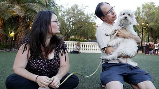 Skye Pearce and Bryan Haas play with their dog, Lucky. The couple says the dog helps fill the void of not having kids.