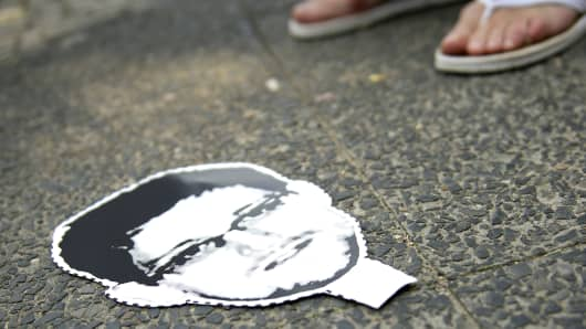 A cardboard mask of Edward Snowden on the ground at a protest against the PRISM surveillance program, which Snowden leaked.
