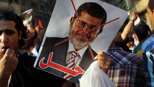 An anti-President Mohammed Morsi poster is viewed as as thousands of Egyptian protesters celebrate in Tahrir Square as the deadline given by the military to Egyptian President Mohammed Morsi passes on July 3, 2013 in Cairo, Egypt.