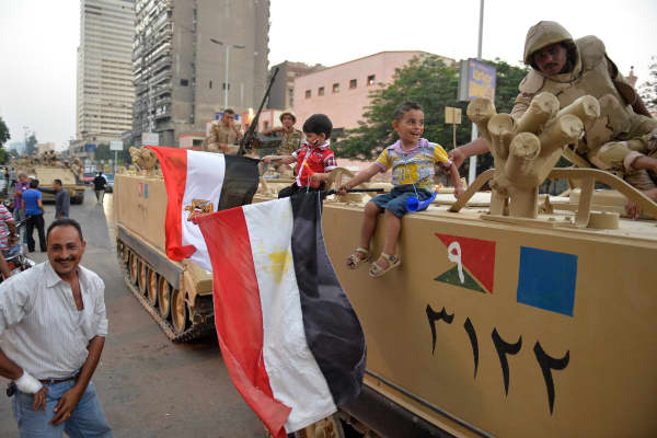 Egyptian children hold national flags as they pose for pictures near army soldiers on an armoured personnel carrier (APC) in a Cairo street on July 3, 2013 after the Egyptian army deployed dozens of armoured vehicles near gathering of Islamist President Mohamed Morsi's supporters.
