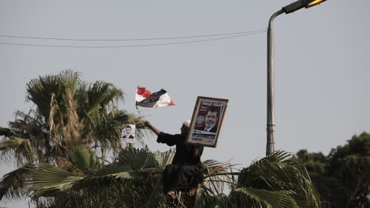 A supporter of Egyptian President Mohammed Morsi holds an Egyptian flag and a poster of Morsi during a demonstration at the Rabaa al Adawiya Mosque in the suburb of Nasr City on July 2, 2013 in Cairo, Egypt.