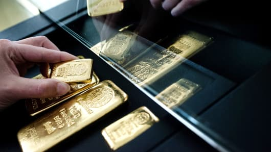 A customer examines a selection of gold bars from Swiss manufacturer Argor Hebaeus SA.