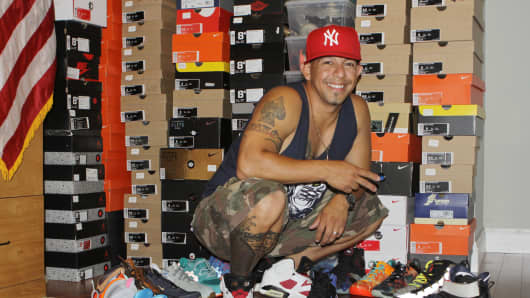 "Jaime Penaloza, a member of an Instagram group called ""Sneakaholics,"" poses with his shoe collection."