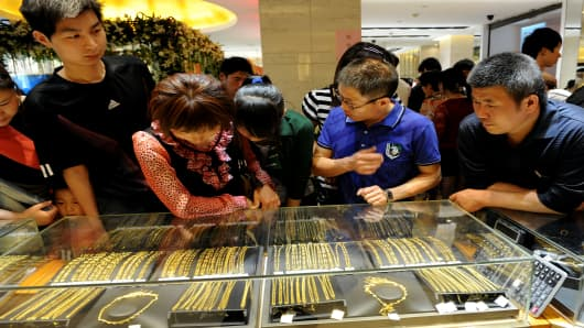 Chinese shoppers look at gold jewellery on display at a shop in Hefei, east China's Anhui province.