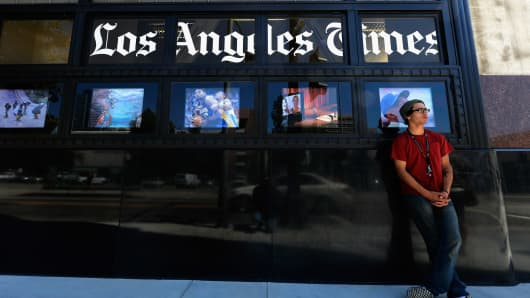 Pedestrians walk past the front of the Los Angeles Times building on June 7, 2012 in Los Angeles, California.