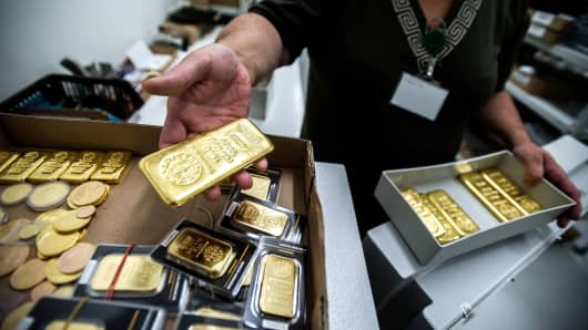 An employee returns a box of One kilogram gold bars to the safe, from Swiss manufacture Argor Hebaeus SA.