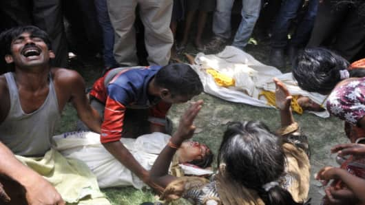 Grief-stricken family members react over the bodies of their children who died after consuming a free mid day meal at a school in India's Bihar state.