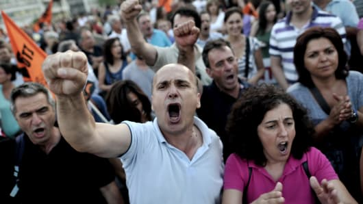 Municipality employees shout slogans against the Greek Government in front of the Greek Parliament during a demonstration as Greek lawmakers prepared to vote late Wednesday on a controversial new austerity package involving a huge shake-up of the civil service with thousands of jobs on the line.