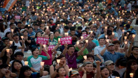 Protesters shout slogans condemning South Korean National Intelligence Service involvement in the country's last presidential elections, during a demonstration outside the Seoul city hall.