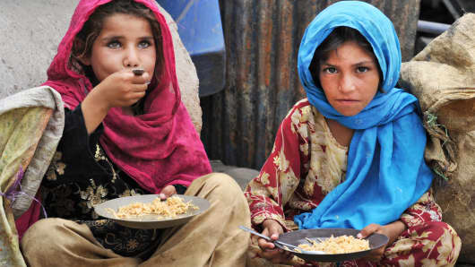 Afghan children, who salvage recyclable items from garbage to make a living, eat a meal of rice in Jalalabad on June 30, 2013.