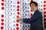 Shinzo Abe, Japan's prime minister and president of the Liberal Democratic Party (LDP), places a red paper rose on an LDP candidate's name to indicate an upper house election victory on Sunday, July 21, 2013.