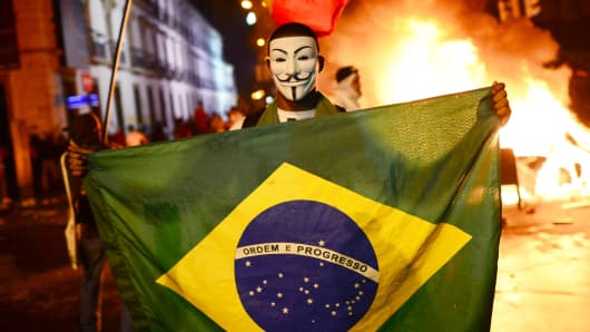A demonstrator wearing a Guy Fawkes mask is seen during clashes in downtown Rio de Janeiro, after a protest over higher transportation fares.
