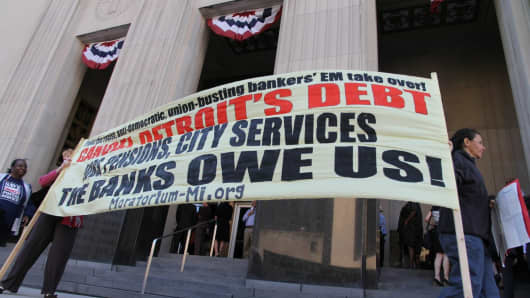 Protesters opposed to bankruptcy proceedings for the city of Detroit gather outside the Theodore Levin United States Courthouse.