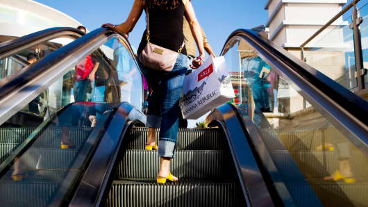 A shopper carries a Banana Republic LLC shopping bag while riding an escalator at the Fashion Valley Mall in San Diego, California, U.S.