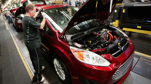 Employee Gary Roberts works on a Ford Motor Co. C-MAX Energi plug-in hybrid vehicle on the production line at the company's assembly plant in Wayne, Michigan.