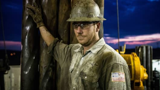 A derrick hand works on an oil rig drilling into the Bakken shale formation outside Watford City, North Dakota.