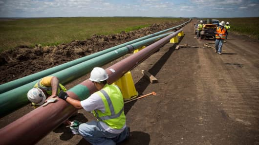 Construction workers specializing in pipe-laying work on a section of pipeline outside Watford City, N.D.