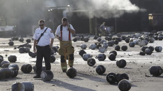 Firefighters walk through an area of exploded propane cylinders in the aftermath of an explosion and fire at a propane gas company, Tuesday, July 30, 2013, in Tavares, Fla.