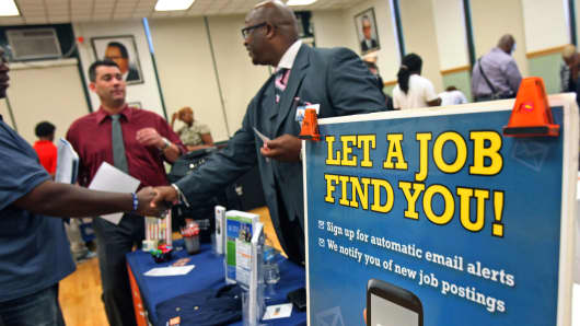 Job seekers speak with an employer at a job fair in Chicago.