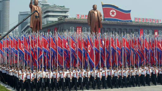 North Koreans wave flags and walk with statues of former leaders Kim Il-Sung and Kim Jong-Il during a military parade past Kim Il-Sung square marking the 60th anniversary of the Korean War armistice in Pyongyang on July 27, 2013.