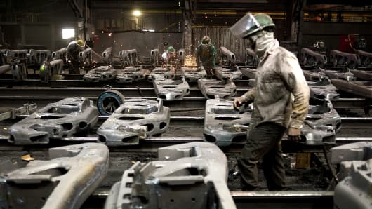 Workers use grinders to smooth down the welded joints on railroad suspension parts at the Columbus Castings finishing area in Columbus, Ohio, U.S.
