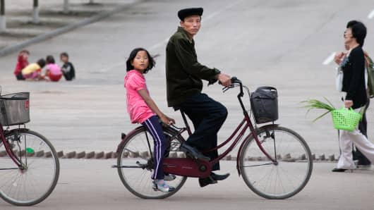 A father and daughter on a bicycle in Rajin, North Korea.