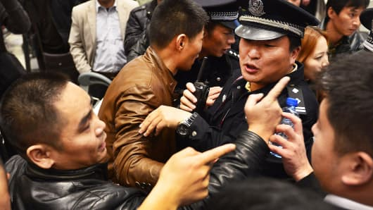 Stranded travellers arguing with police (R) and airline personnel at Changshui International Airport in Kunming, China, January, 2013.