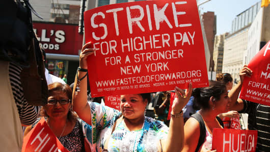 Fast-food workers demand higher pay at a protest outside a Wendy's in New York in July.