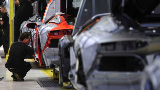 Workers assemble Aventador automobiles on the production line at the Lamborghini factory near Bologna, Italy.
