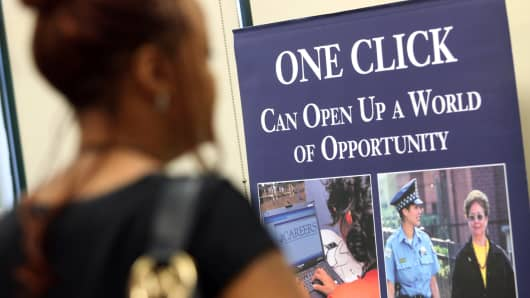 Signage for employment with the City of Chicago is visible beyond job seeker at a job fair in Chicago, Illinois.