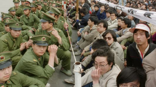 Several hundred of 200,000 pro-democracy student protesters face to face with policemen outside the Great Hall of the People in Tiananmen Square 22 April 1989 in Beijing.