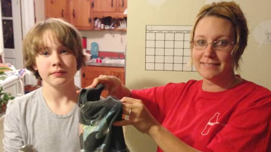 Rachel Farmer and her son, Christopher, bag up some clothing to send to Schoola Stitch. They hope to raise money for his school in Bowling Green, Va.