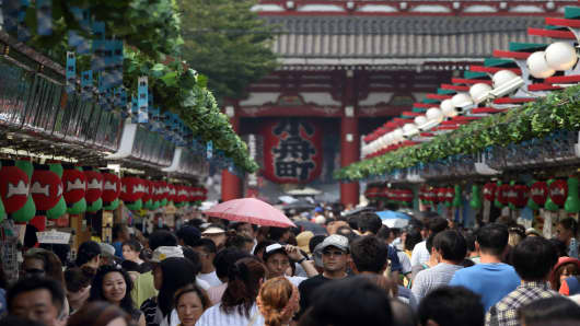 Shoppers and tourists walk through a shopping street in front of the Sensoji temple in Tokyo, Japan, on Thursday, Aug. 8, 2013.